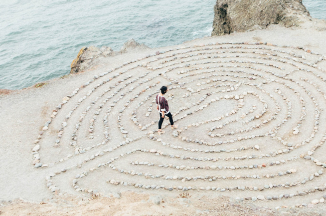 woman walks to center of beach labyrinth