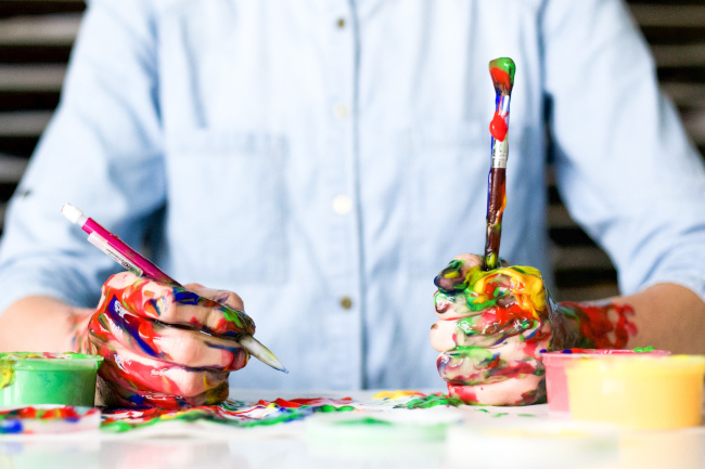 man with paint-covered hands for outsourced creativity